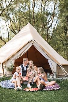 Openluchtportret van gelukkige familie, vader, moeder en twee kleine dochters, zittend op het gras en genietend van watermeloen bij de picknick bij kampeertent