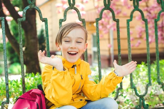 Openluchtportret van gelukkige student met rugzak. jonge student begin van de klas na vakantie. terug naar schoolconcept. leuke jongen buiten op school die plezier heeft.