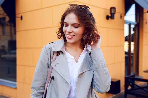 Openluchtportret van glimlachend gelukkig kortharig meisje met perfecte witte tanden die pret hebben. winderige haren. herfst stemming.