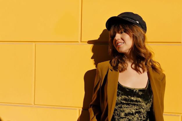 Openluchtportret van glimlachende mooie vrouw met krullend kapsel die jasje en glb dragen die over gele muur stellen