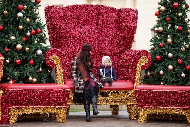 Openluchtportret van glimlachende vrouw en meisje in kerstmisdecoratie op straat van stad. gelukkig gezin met klein kind. winter- en kerstvakantie concept.