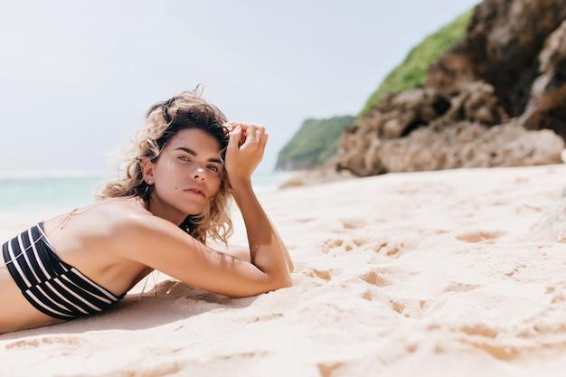 Openluchtportret van goedgehumeurde dame die op aard koelen. foto van kaukasische vrolijke vrouw die op zandig strand ligt.