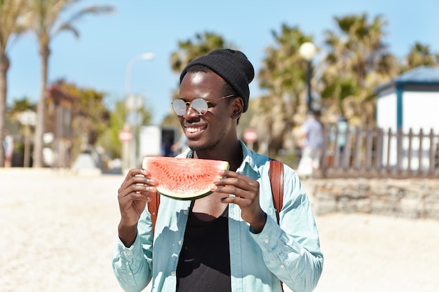 Openluchtportret van het aantrekkelijke jonge segment van de studentenholding van rijpe sappige watermeloen