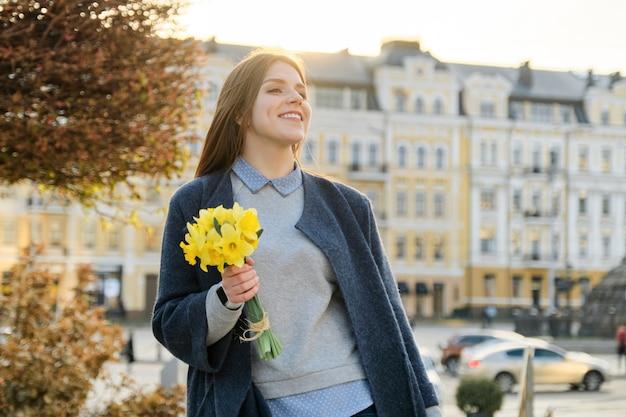 Openluchtportret van jong mooi meisje met boeket van gele de lentebloemen