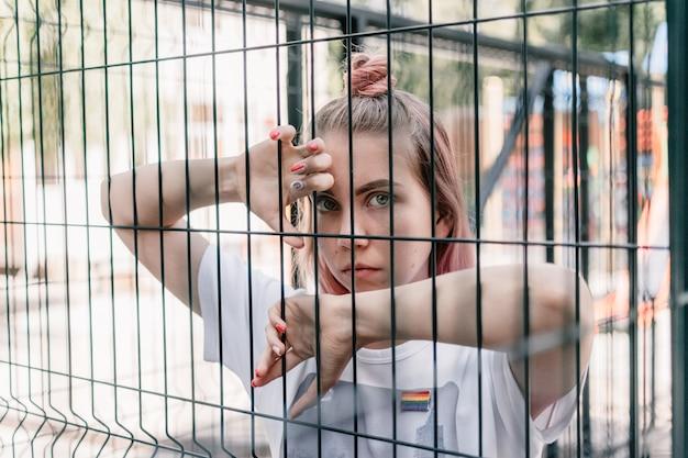 Openluchtportret van jong tiener hipster meisje met roze haar en lgbt teken