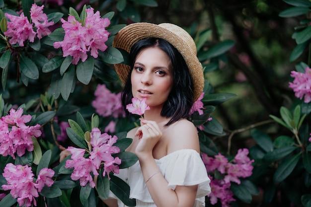 Openluchtportret van jonge mooie gelukkige glimlachende vrouw in strohoed het stellen dichtbij bloeiende boom.
