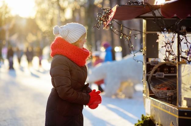 Openluchtportret van jonge mooie vrouw bij de winterstad