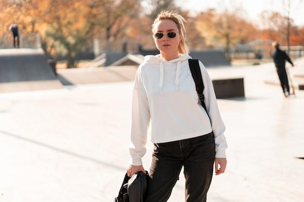 Openluchtportret van jonge mooie vrouw met een paardestaart en zonnebril, met een rugzak op zijn schouders, gekleed in een witte sweater, dichtbij het sportterrein. witte hoodie