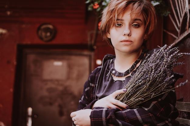 Openluchtportret van jonge mooie vrouw met kort rood haar poseren met lavendelbloem. levensstijl in de stad. meisje in de oude stad met rode muren Premium Foto