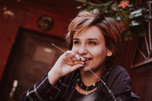 Openluchtportret van jonge mooie vrouw met kort rood haar poseren met lavendelbloem. levensstijl in de stad. meisje in de oude stad met rode muren