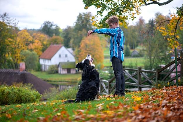 Openluchtportret van jongen met berner sennenhond in de herfst. vriendschap van tiener met huisdier.