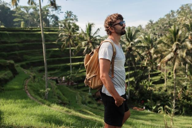 Openluchtportret van knappe reismens die met rugzak op stijgingsterras in bali lopen.