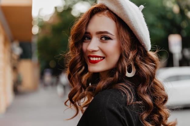 Openluchtportret van lachende gembervrouw met rode lippen die van de herfstochtend genieten. debonair franse dame in baret terugkijkend.