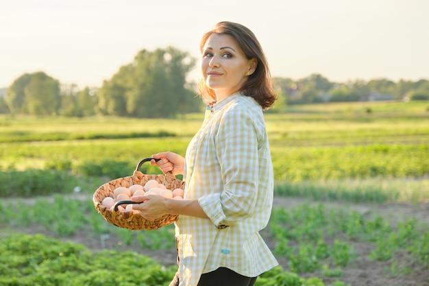 Openluchtportret van landbouwersvrouw met mand van verse kippeneieren, landbouwbedrijf