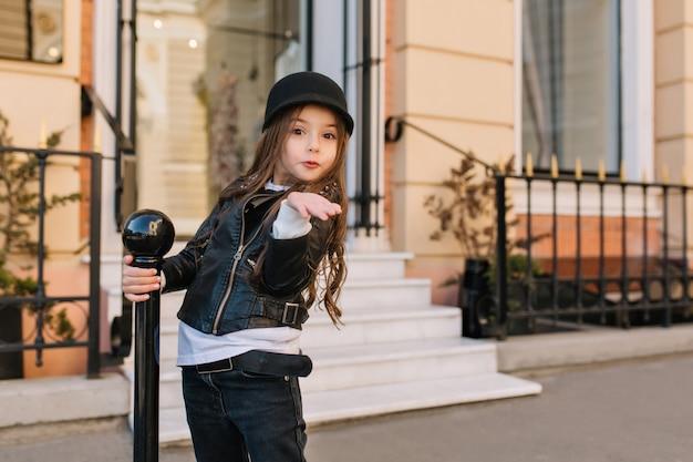 Openluchtportret van leuk klein meisje die in hoed luchtkus met verbaasde gezichtsuitdrukking verzenden.