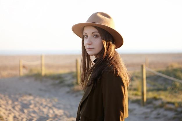 Openluchtportret van modieuze jonge europese vrouw die trendy hoed en zwarte jas dragen die met subtiele glimlach kijken terwijl het hebben van aardige avondwandeling aan zee, dromend en zonsondergang bewonderen