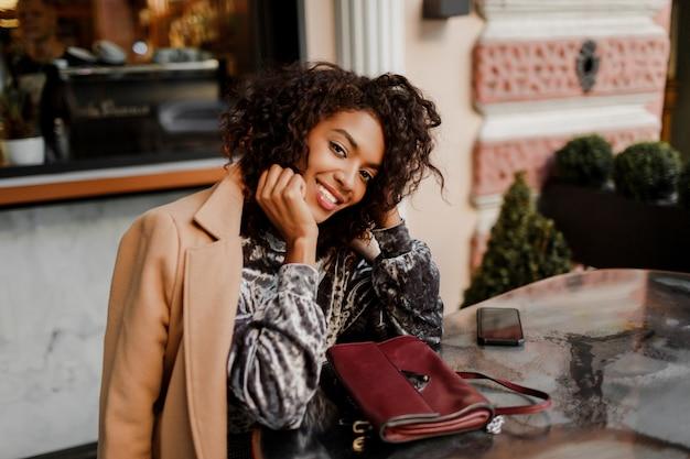 Openluchtportret van mooi glimlachend zwarte die met modieuze afroharen in koffie in parijs zitten.