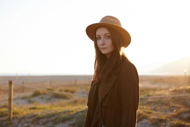 Openluchtportret van mooi kaukasisch vrouw die modieuze jas en hoed dragen die zorgeloos en vreedzaam voelen, overwinnend verbazingwekkend ochtendmening aan kust, kijkend met charmante glimlach