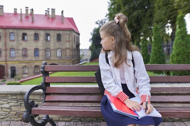 Openluchtportret van mooi meisje dat met rugzak in notitieboekje schrijft
