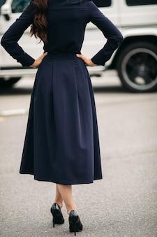 Openluchtportret van mooie modieuze dame die zich tegen de auto op de achtergrond bevindt. vrouwelijke mode. stadslevensstijl