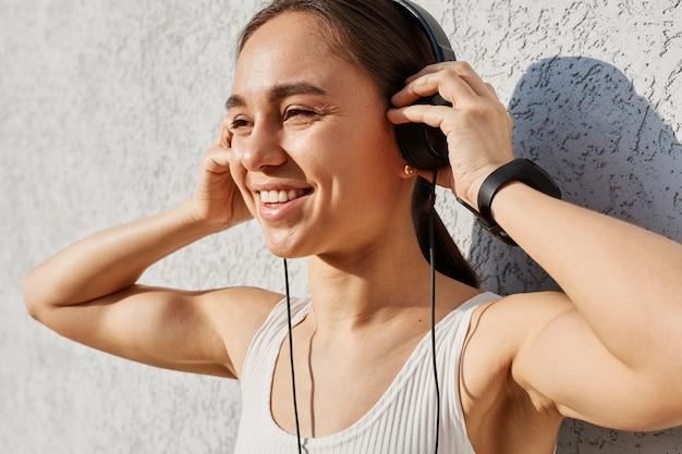 Openluchtportret van mooie tevreden positieve gelukkige vrouw die witte bovenkant draagt, die muziek luistert