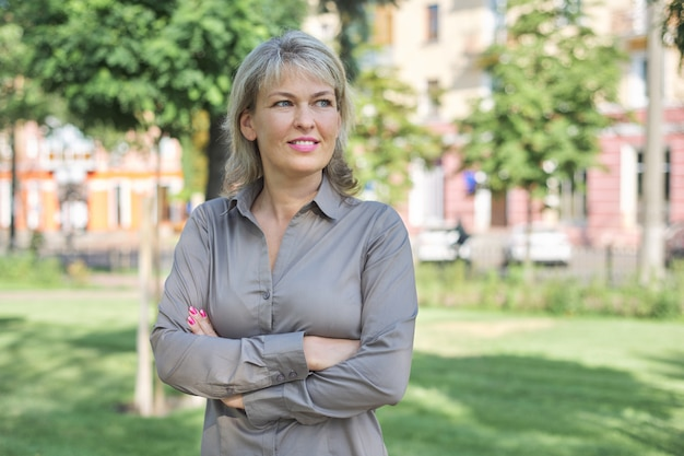 Openluchtportret van positieve rijpe vrouw op middelbare leeftijd