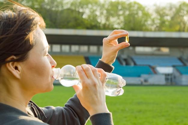 Openluchtportret van rijpe vrouw die vitamine e nemen