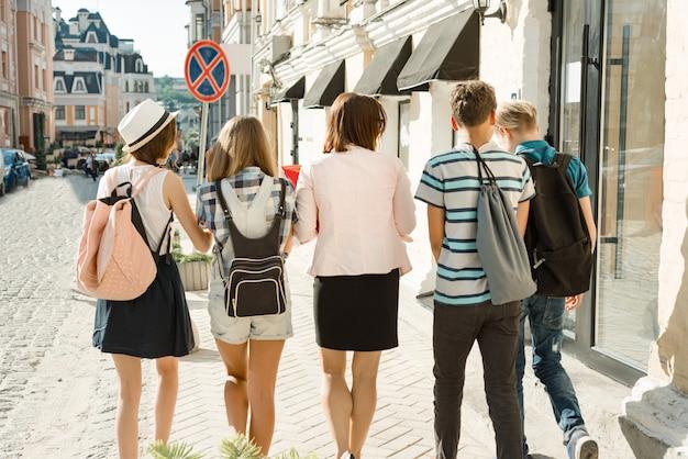 Openluchtportret van schoolleraar en groep tieners