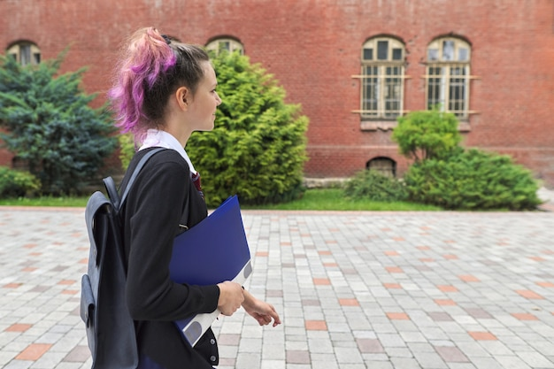 Openluchtportret van schoolmeisje dichtbij schoolgebouw