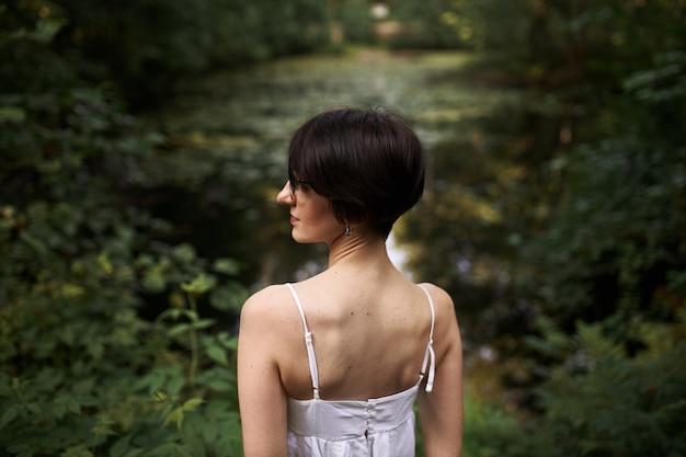 Openluchtportret van tedere kortharige jonge blanke vrouw met bleke huid en slank lichaam ontspannen door vijver in nationaal park
