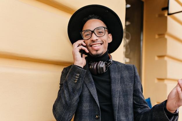 Openluchtportret van tevreden afrikaanse mens die in wollen jasje vriend roept. gelukkig zwarte man in hoed praten over de telefoon terwijl hij in de buurt van geel gebouw staat.