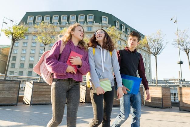 Openluchtportret van tienerstudenten met en rugzakken die lopen spreken.