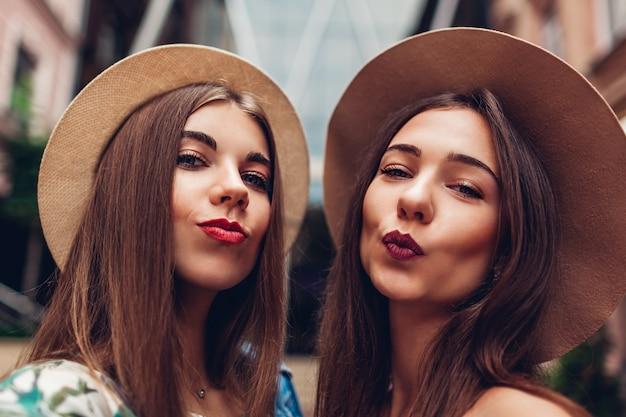 Openluchtportret van twee jonge mooie modieuze vrouwen die selfie nemen. meisjes met plezier in de stad. beste vrienden
