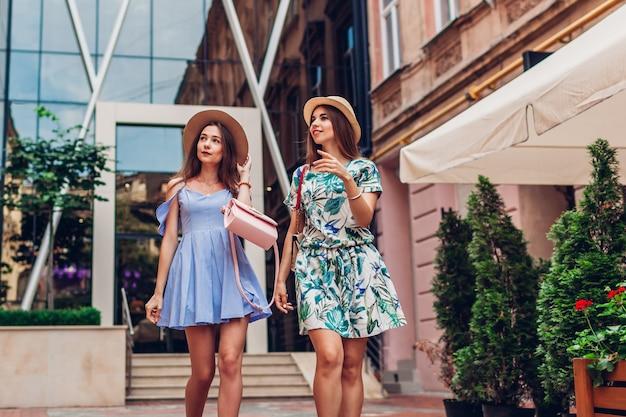 Openluchtportret van twee jonge mooie vrouwen die op stadsstraat lopen. beste vrienden hangen, plezier maken