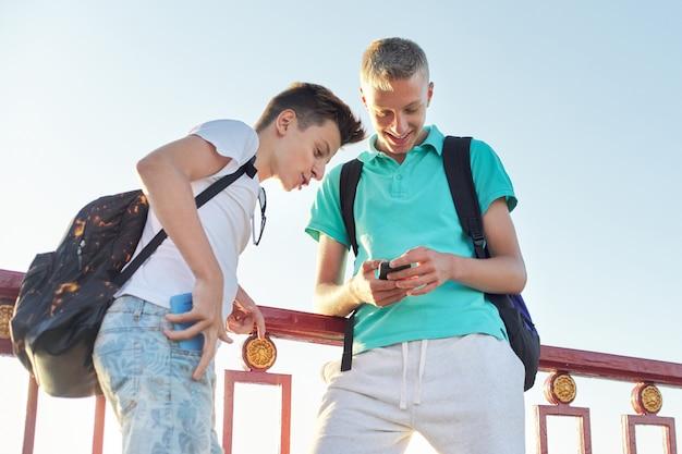 Openluchtportret van twee sprekende jongenstieners 15, 16 jaar oud