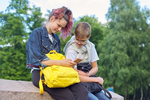 Openluchtportret van twee sprekende tieners met smartphone