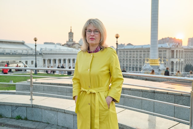 Openluchtportret van volwassen vrouw met bril, gele regenjas