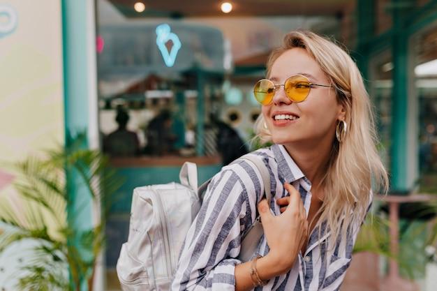 Openluchtportret van vrij blonde vrouw die oranje bril met rugzak draagt