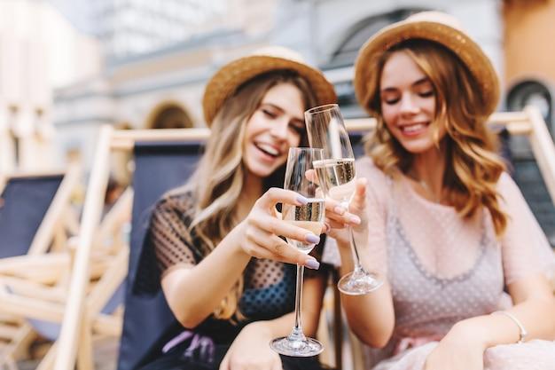 Openluchtportret van vrolijke jonge vrouwen die vakantie vieren met bekers champagne op voorgrond