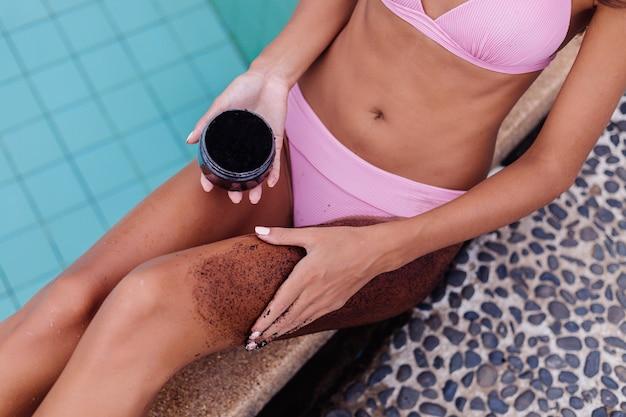 Openluchtportret van vrouw in roze bikini bij kuuroord door de koffiescrab van de zwembadholding