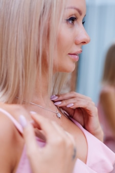 Openluchtportret van vrouw in roze romantische kleding die halsband draagt