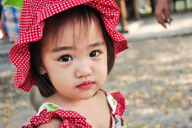 Openluchtportret van weinig aziatisch meisje dat rode hoed draagt