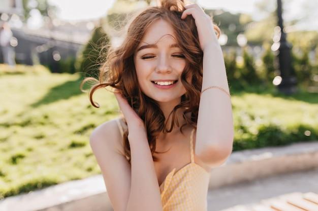 Openluchtportret van wit innemend meisje met rood krullend haar die zich voordeed op aard. glimlachende schitterende gembervrouw die zich met gesloten ogen in park bevindt.