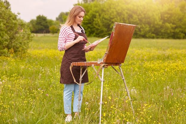 Openluchtschot van chrming meisje met borstel en palet van verven die aan weide in mooi landschap werken, wijfje dat gestreept overhemd draagt