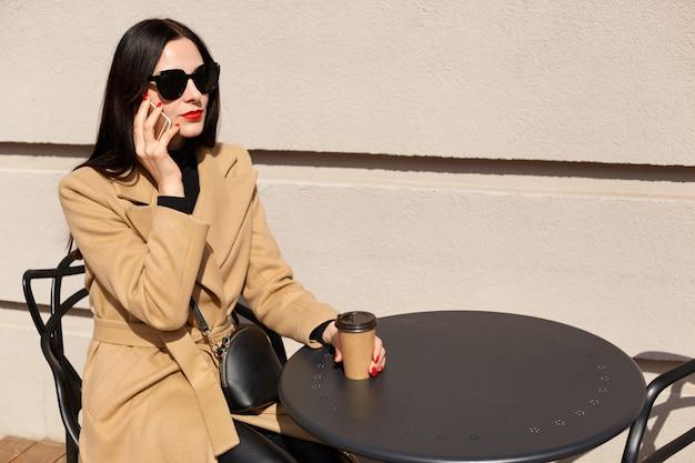 Openluchtschot van mooie slanke vrouw die heldere make-up hebben, die bij lijst zitten, papercup met hete drank houden, gesprek over mobiele telefoon hebben, toebehoren dragen, die geconcentreerd zijn.