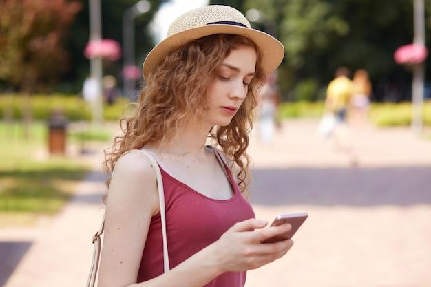 Openluchtschot van peinzend leuk jong wijfje dat haar mobiele telefoon in één hand houdt