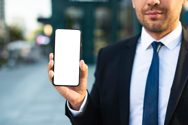 Openluchtzakenman die een lege mobiele telefoon houdt