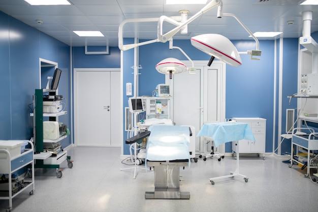 Operatiekamer in hedendaagse klinieken inclusief operatietafel omgeven door lampen, diagnoseapparatuur en set lades