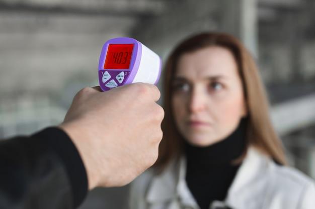 Operator controleert koorts door bezoeker van digitale thermometer bij informatiebalie om te scannen en te beschermen tegen coronavirus covid-19