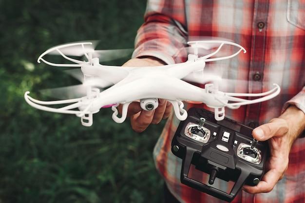 Operator met afstandsbediening en quadrocopter.